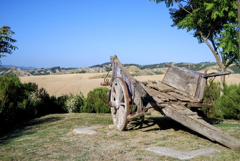 Vieux chariot en bois rustique donnant sur un champ de ferme image libre de droits