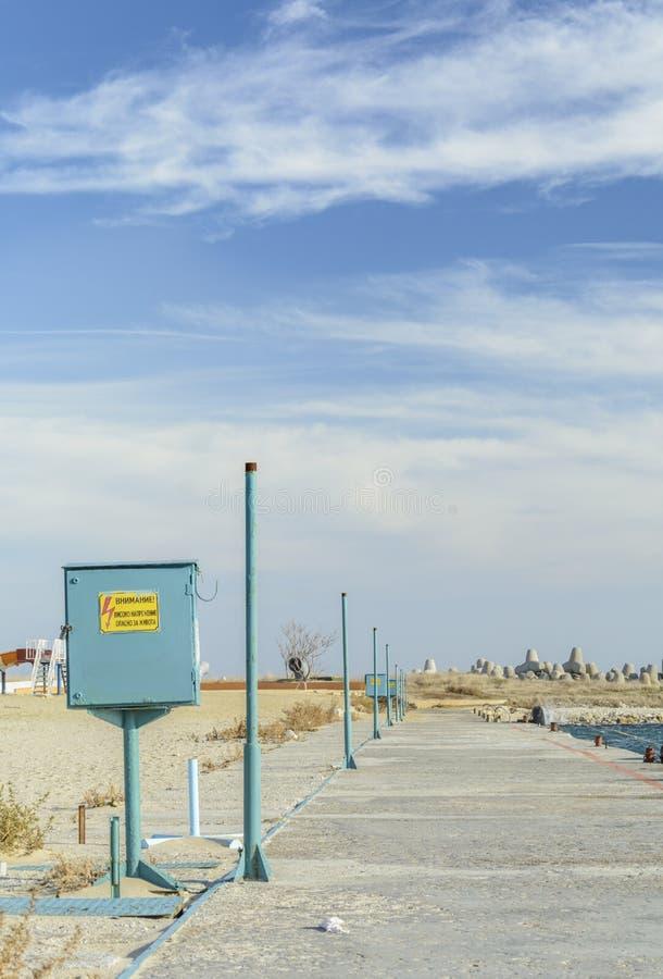 Vieux chemin concret dans le bord de la mer avec une ligne de transforme rouillé images libres de droits