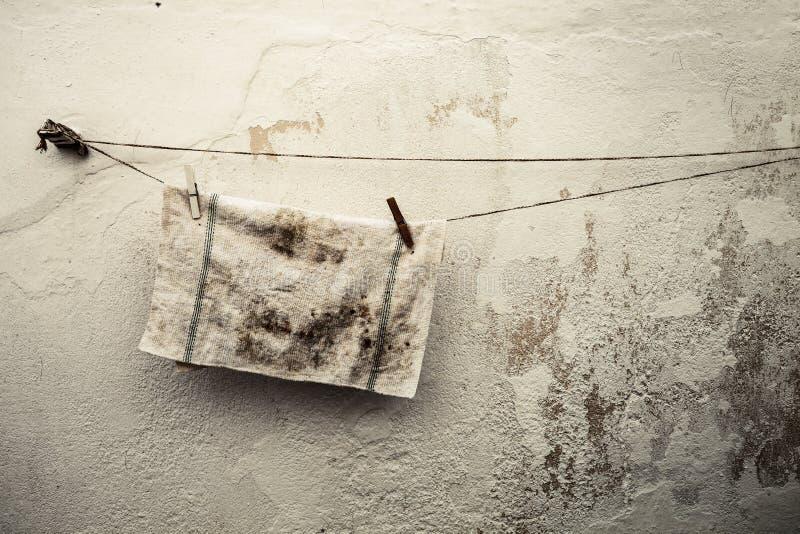 Vieux chiffon sale accrochant sur un fil Fond antique de mur photographie stock libre de droits