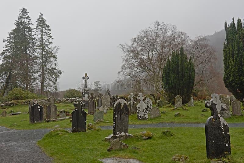 Vieux cimetière dans le brouillard dans le site monastique de Glendalough photographie stock libre de droits