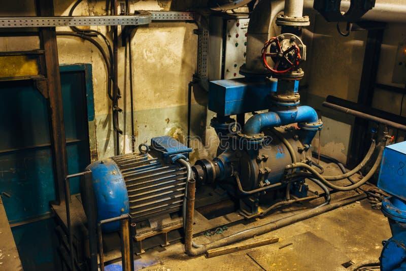 Vieux compresseur électrique industriel dans la cave sous l'usine image stock