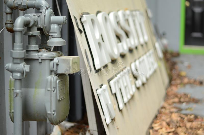 Vieux compteur à gaz à côté d'un signe abandonné de crossfit photo stock
