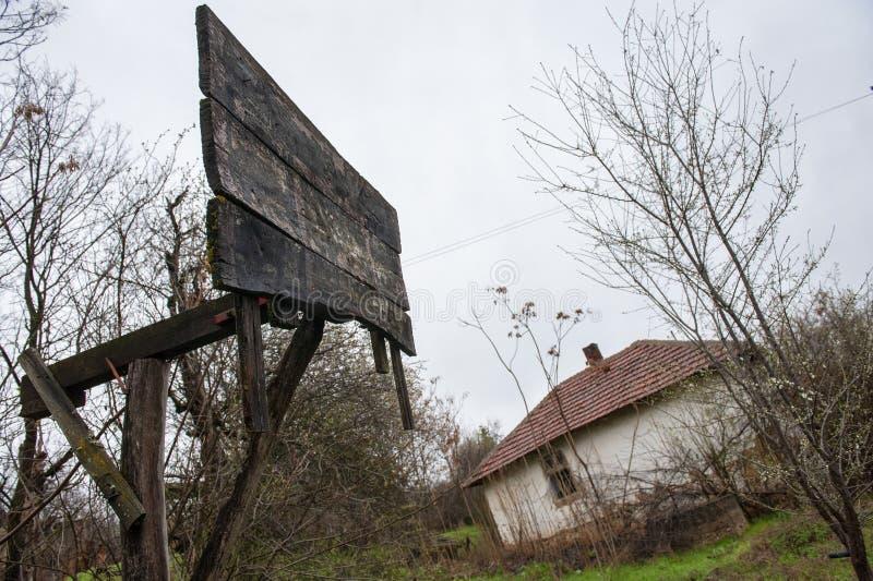 Vieux conseil endommagé de basket-ball devant la maison abandonnée par cru dans la campagne image stock