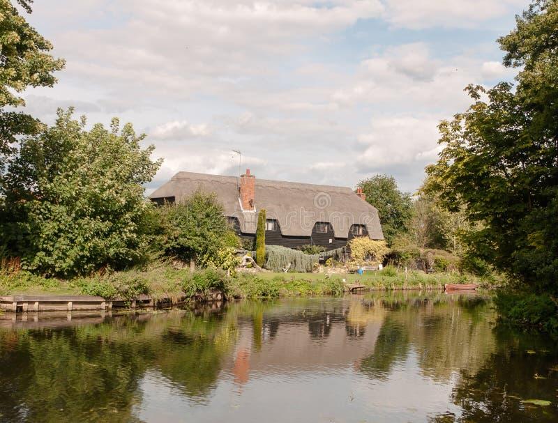 Vieux cottage historique anglais vu au-dessus d'un lac avec des réflexions photos libres de droits
