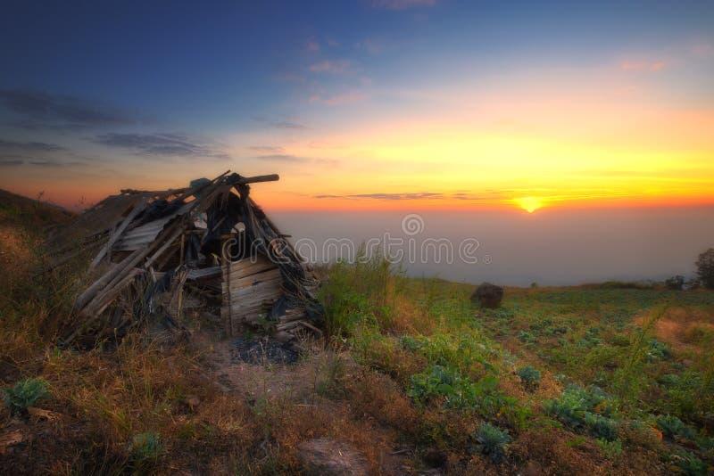 Vieux cottage sur le champ de chou avec la vue de lever de soleil images stock