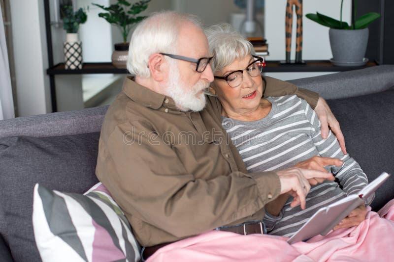 Vieux couples curieux discutant la belle mémoire se reposant sur le sofa image stock