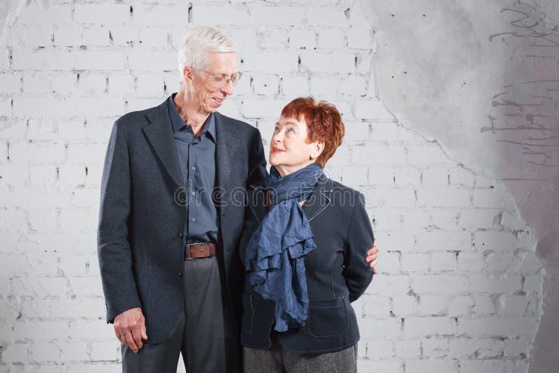 Vieux couples de sourire heureux tenant la caresse ensemble d'isolement sur le fond blanc de brique Copiez l'espace photographie stock libre de droits