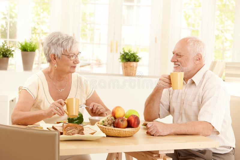 Vieux couples heureux prenant le petit déjeuner photographie stock