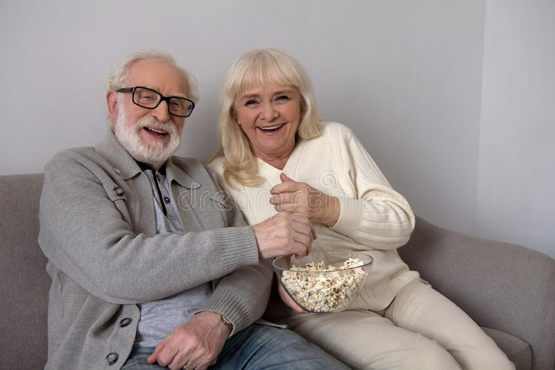 Vieux couples mangeant du maïs éclaté sur le sofa images libres de droits