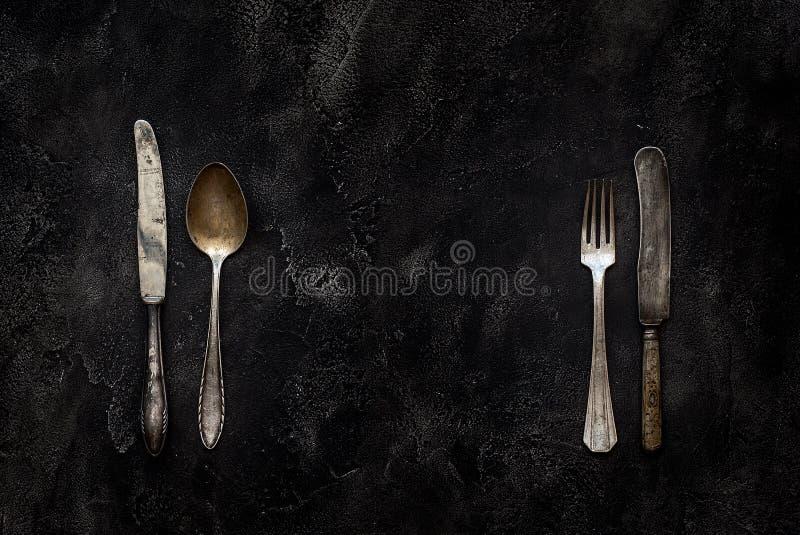 Vieux couteau, cuillère et fourchette de grange sur la vue supérieure concrète photos stock