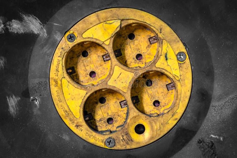 Vieux débouché électrique jaune en gros plan portatif image stock