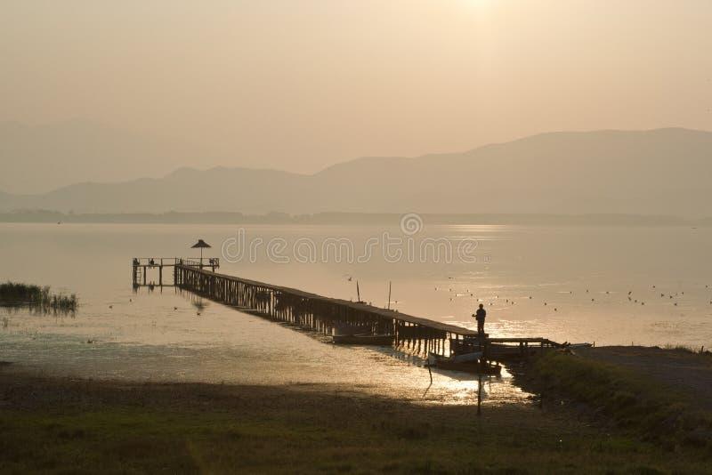 Vieux dock en bois sur le lac Dojran au coucher du soleil photo stock