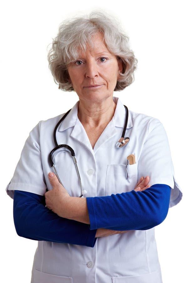 Vieux docteur avec des bras croisés images stock