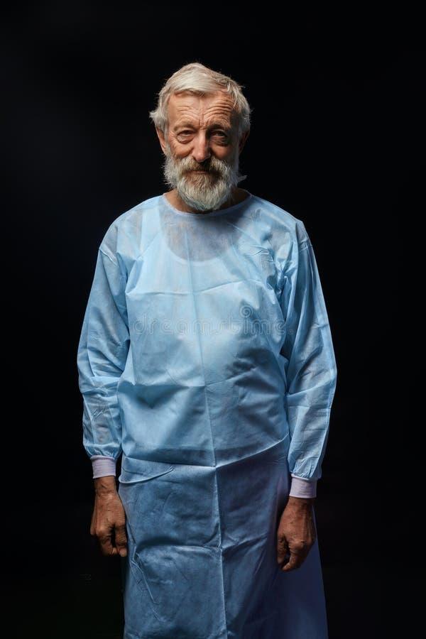 Vieux docteur beau dans l'uniforme spécial posant à la caméra images libres de droits