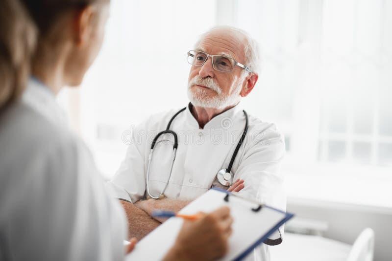 Vieux docteur regardant l'infirmière tout en se tenant dans la chambre d'hôpital photographie stock