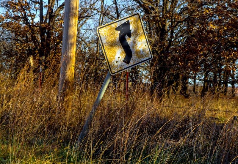 Vieux et criqué signe de courbe en avant inclinant en longueur le long d'une route de campagne dans la fin de l'après-midi avec l image stock