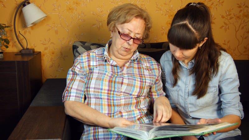 Vieux et jeune femme regardant l'album photos de famille image stock