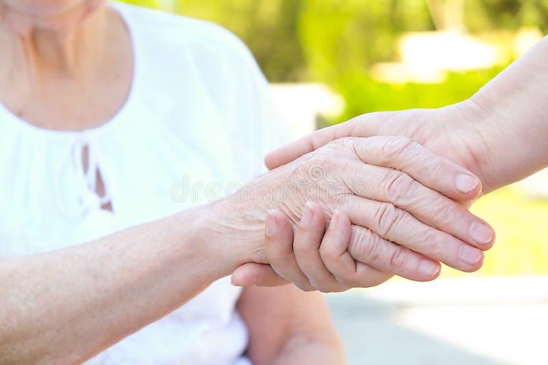 Vieux et jeunes tenant des mains sur la fin légère de fond  Coups de main, concept de soin aux personnes âgées image libre de droits