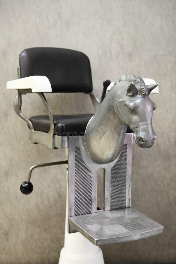 Vieux fauteuil de coiffeur d'enfant photographie stock