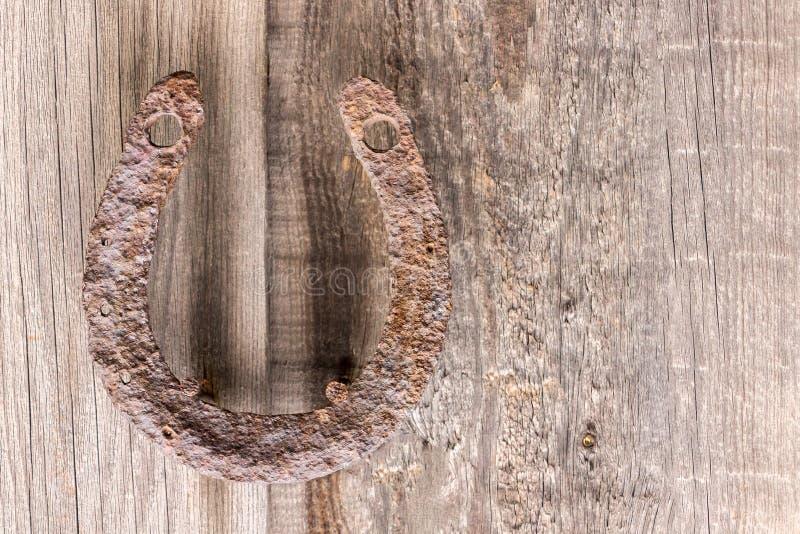 Vieux, fer à cheval rouillé d'antiquité, fixe sur des clous sur une vieille surface en bois photo libre de droits