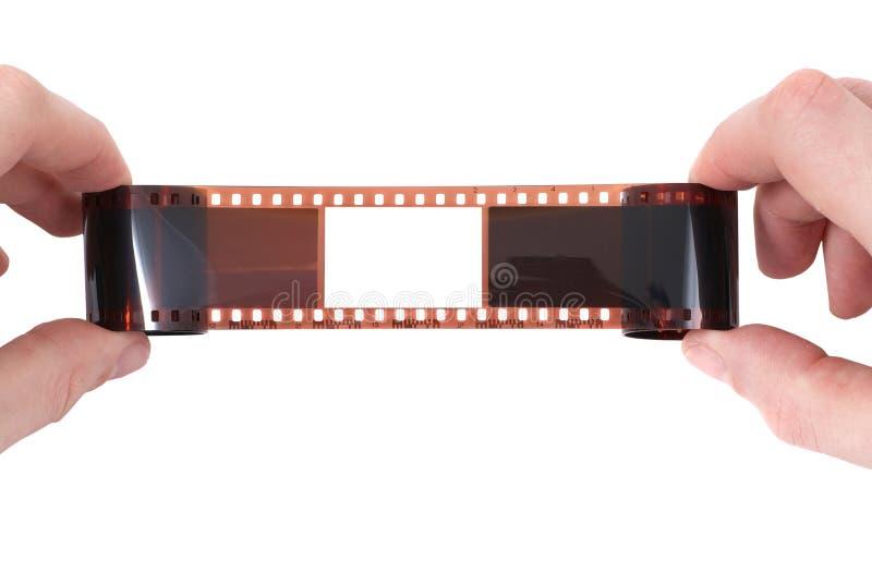 Vieux film avec la trame vide dans les mains photographie stock libre de droits