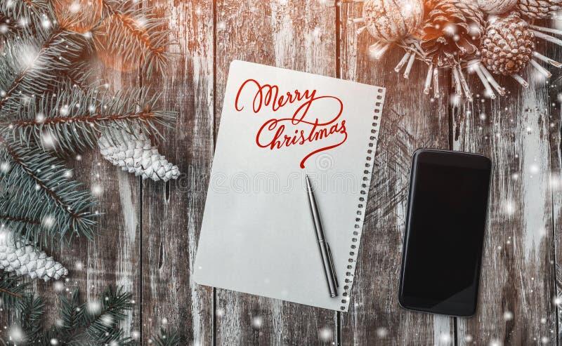 Vieux fond en bois, arbre de sapin vert avec les cônes blancs, un panier de cône, message de Joyeux Noël et téléphone images libres de droits