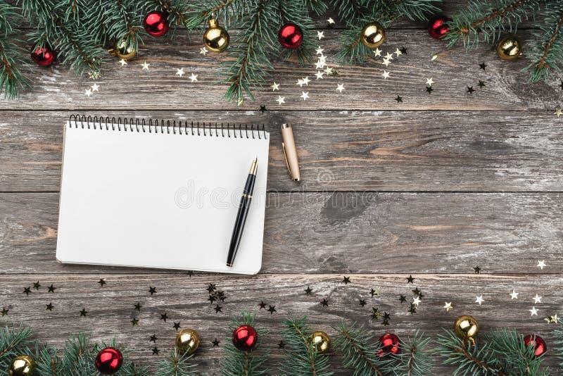 Vieux fond en bois de Noël Branches de sapin avec des babioles et des étoiles d'or Livre de félicitation de Noël Vue supérieure photographie stock
