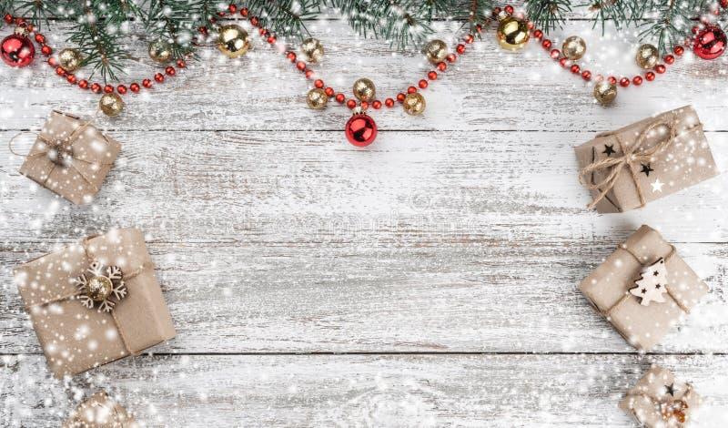 Vieux fond en bois de Noël Branches de sapin Or et babioles rouges Guirlandes et cadeaux rouges Vue supérieure L'espace pour votr photos stock
