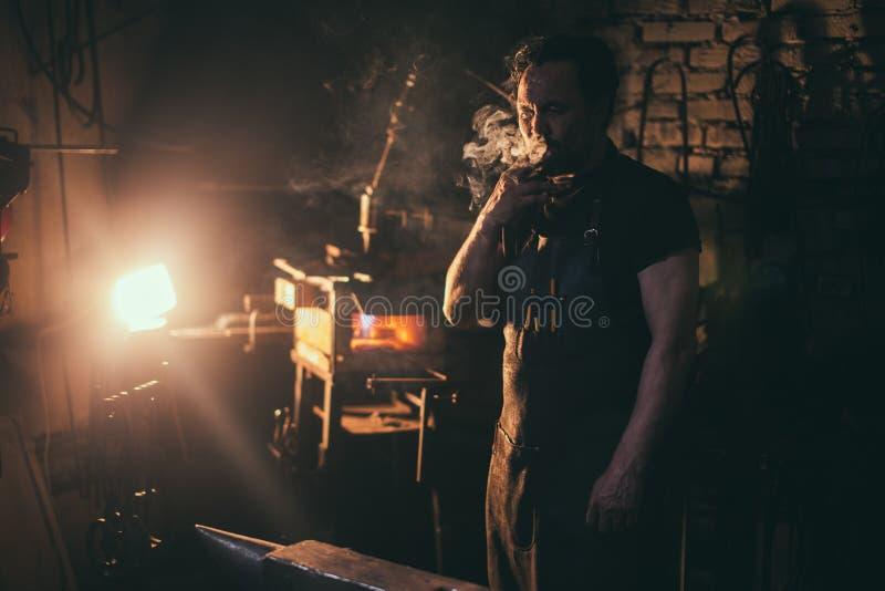 Vieux forgeron occidental Smokes un cigare image stock