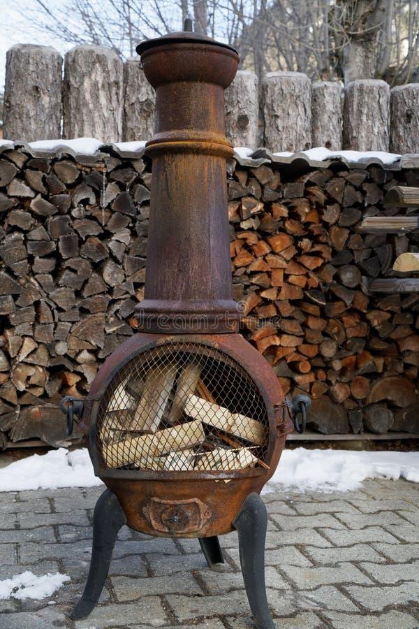 Vieux fourneau brûlant en bois de vintage avec des rondins à l'intérieur de prêt pour worming photographie stock
