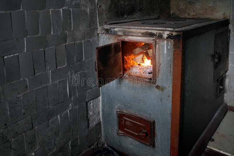 Vieux fourneau en bois rural avec le bois de chauffage brûlant image stock
