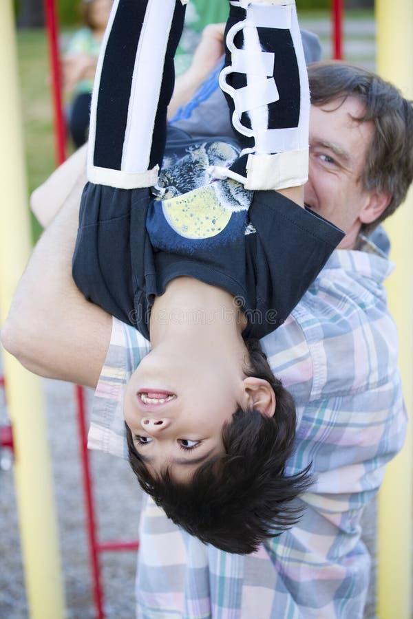 Vieux garçon de cinq ans handicapé sur les bars de singe photos stock