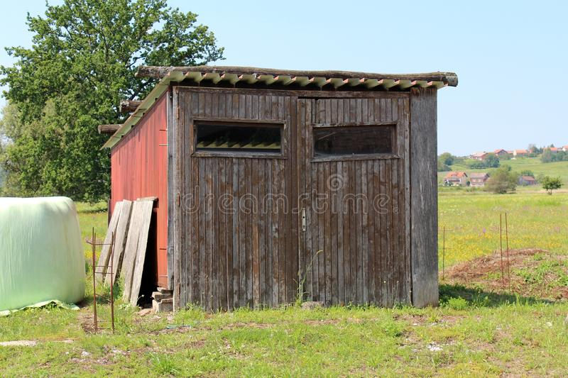Vieux garage en bois maintenant utilisé comme hangar de jardin pour stocker des outils entourés avec l'herbe et les maisons non c photo libre de droits