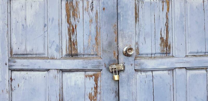 Vieux grunge ou porte ou fenêtre en bois bleu-clair de cru verrouillée avec la petite clé machine d'or pour le fond photographie stock libre de droits