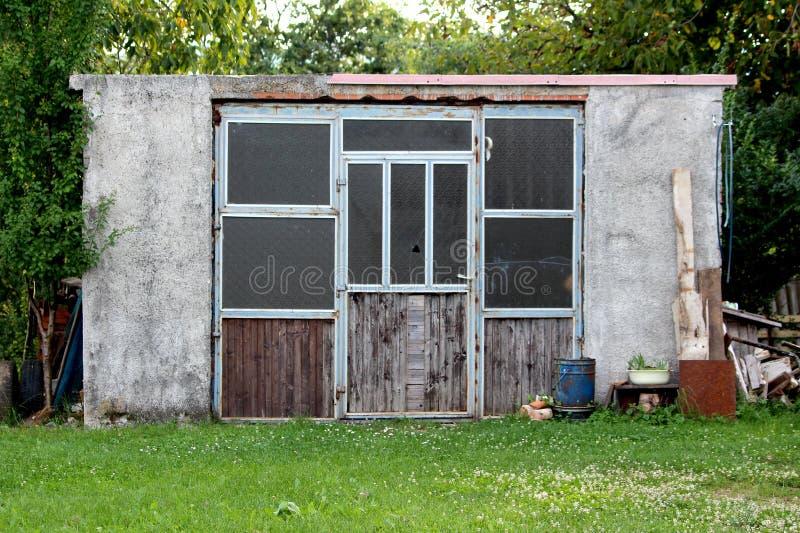 Vieux hangar concret fait maison de jardin avec l'ordure jetée d'arrière-cour dans les arbres avant et hauts à l'arrière-plan photo stock