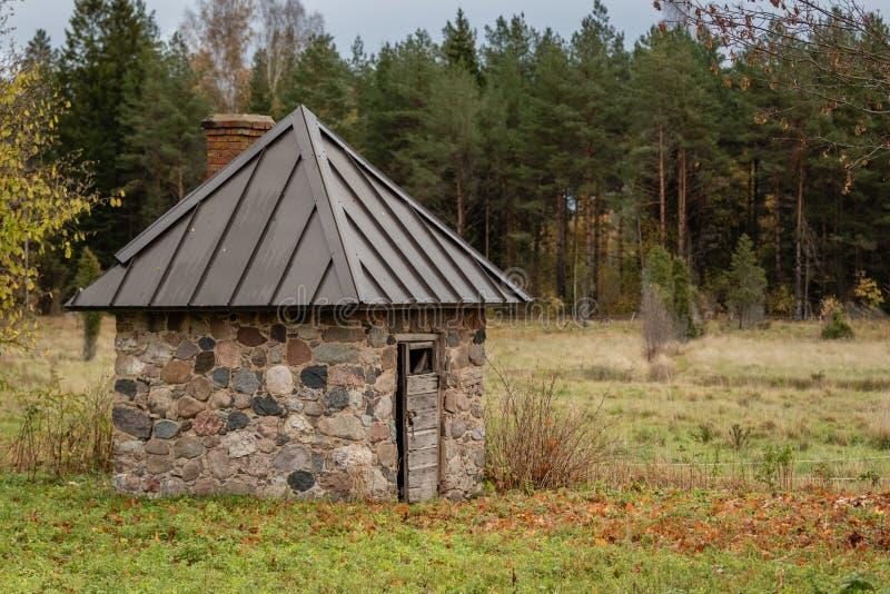 Vieux hangar en pierre avec le nouveau toit à une ferme un jour rainny dans la zone rurale de la Lettonie photographie stock libre de droits