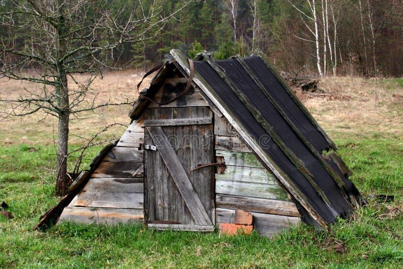 Vieux hangar rustique en bois au milieu d'un champ par la forêt photographie stock libre de droits