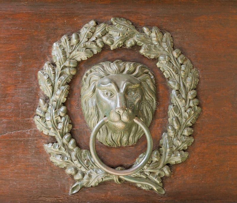 Vieux heurtoir de porte en bronze - la tête et le chêne de lion tressent photos stock