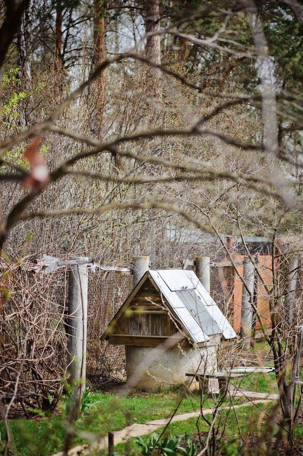Vieux jardin rustique de puits d'eau au printemps image libre de droits