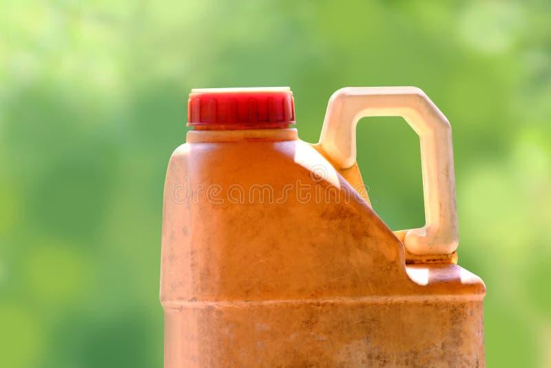 Vieux jaunes de gallon en plastique du lubrifiant d'huile sur le fond vert brouillé, se ferment vers le haut du vieux et sale gal image stock