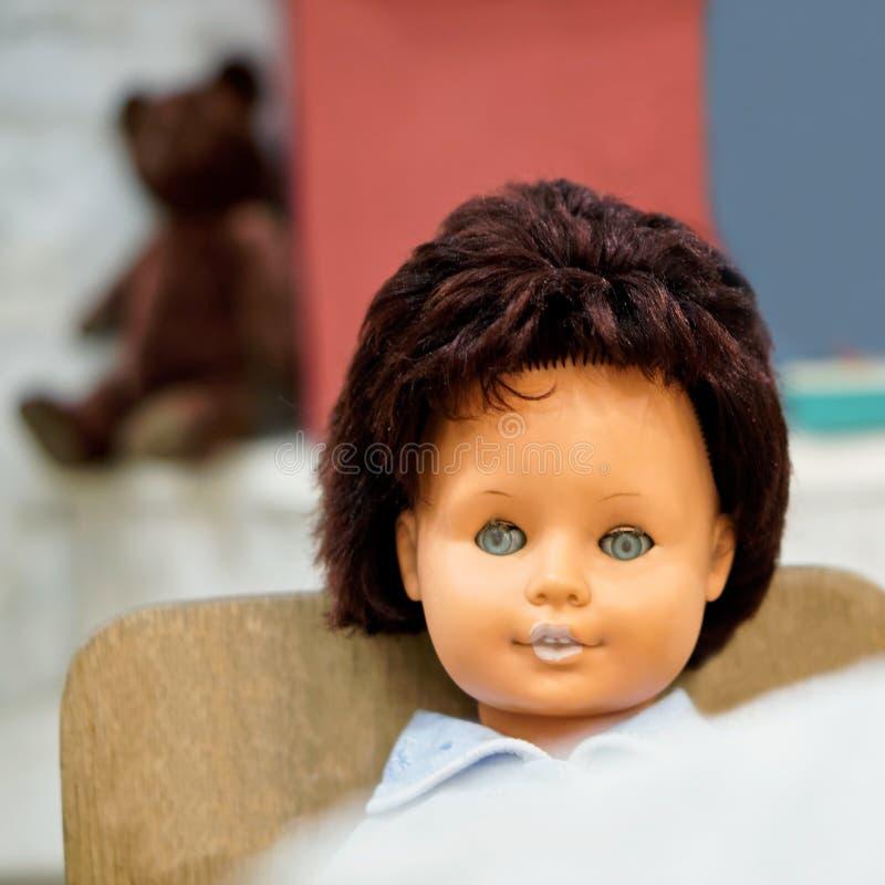 Vieux jouet - une poupée de cru avec des yeux bleus se repose devant une table dans un highchair Profondeur de zone images stock