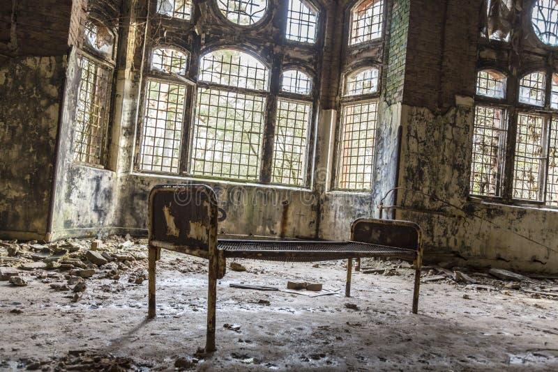 Vieux lit rouillé dans la maison ruineuse photographie stock