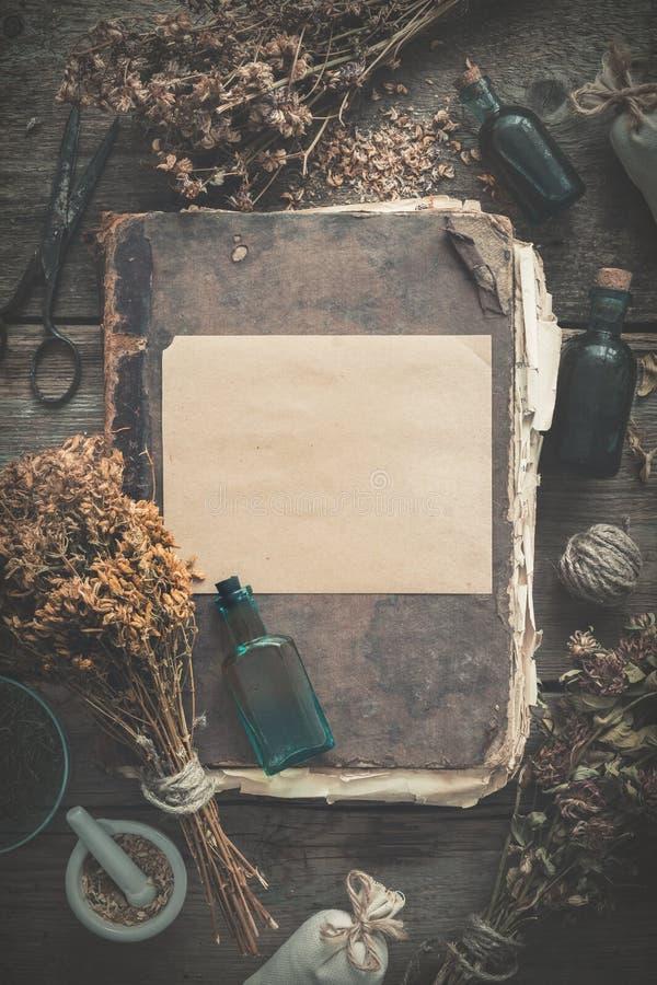 Vieux livre antique, bouteilles de teinture, groupes d'assortiment des herbes saines sèches, mortier Le perforatum de fines herbe image stock