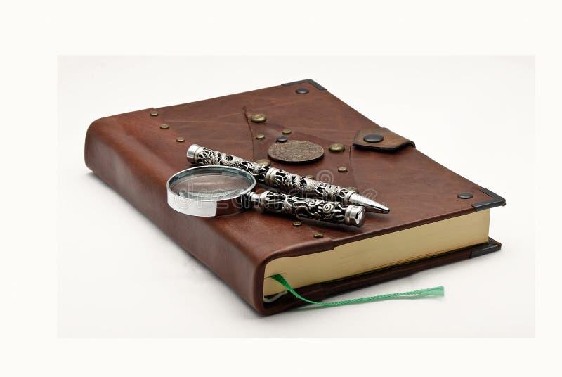 Vieux livre avec un crayon lecteur et une loupe photographie stock