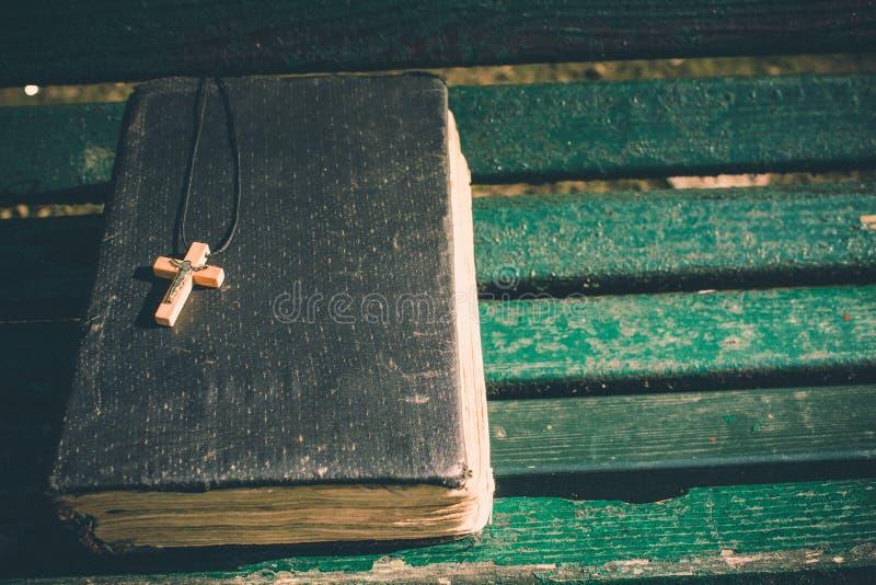 Vieux livre de Sainte Bible de vintage, couverture texturisée grunge avec la croix chrétienne en bois Rétro image dénommée sur le photographie stock