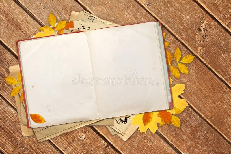 Vieux livre et feuilles d'automne sur les conseils en bois images stock