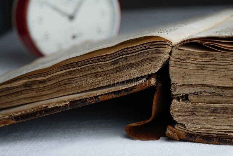 Vieux livre et horloge analogique. photographie stock