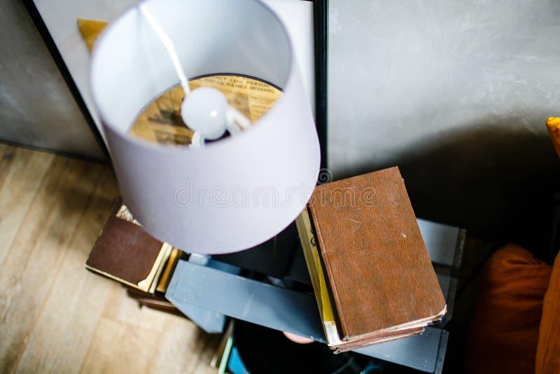 Vieux livre et lampe blanche sur la table de chevet photos libres de droits