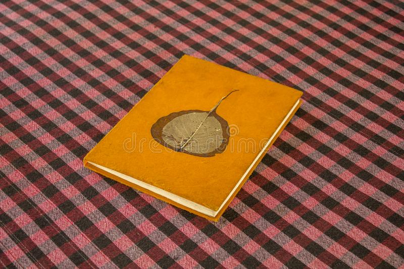 Vieux livre orange lumineux minable avec une feuille s?che grise sur les mensonges de couverture sur une table noire blanche roug photo stock