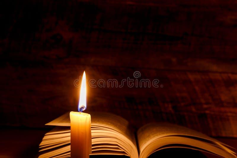 Vieux livre sur une table en bois par lueur d 39 une bougie for Une fenetre une bougie